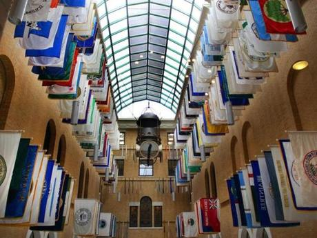 Municipal flags line the Great Hall at the State House, but not all Massachusetts towns are represented.